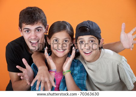 Surprised Siblings with Big Brother on orange background - stock photo