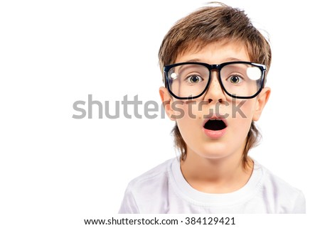 Surprised smart boy in big glasses staring at the camera. Education. Studio shot. Isolated over white. - stock photo