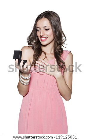 Surprised smiling beautiful woman holding an open jewelery gift, white background. - stock photo