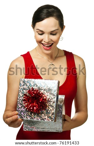 Surprised smiling beautiful young woman holding an open jewelery gift box and looking at the present.