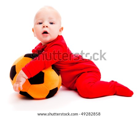 Surprised soccer baby in red holding ball in hands - stock photo