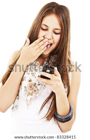 Surprised teen girl looking at the mobile phone in her hand. Isolated on white background. - stock photo