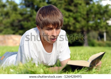 Surprised Teenager lying on the Grass and reads a Book in the Summer Park - stock photo