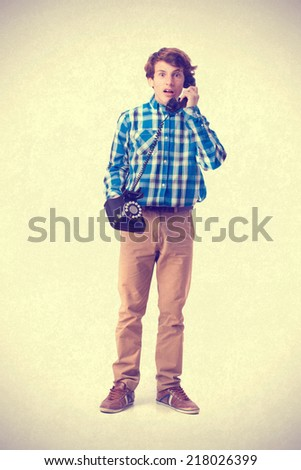 surprised teenager talking by phone - stock photo