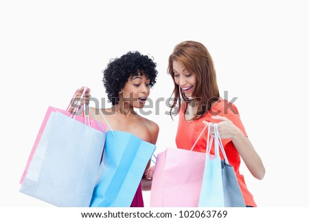 Surprised teenagers proudly showing their purchases to each other - stock photo