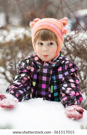 Surprised toddler girl plaing with snow in winter park - stock photo