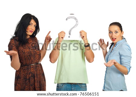 Surprised two women pointing to unknown guy who hold a question mark in front of his face isolated on white background - stock photo