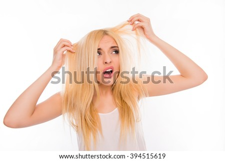Surprised unhappy young woman looking at her damaged hair - stock photo