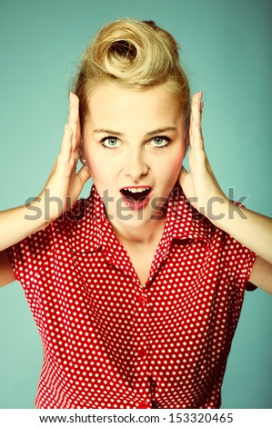 surprised woman face, beautiful girl in retro style holding her head in amazement and open-mouthed blue background - stock photo