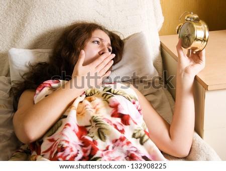 Surprised woman holding alarm clock - stock photo