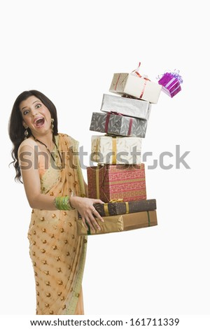 Surprised woman holding Diwali gifts - stock photo