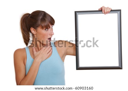 surprised woman holding empty picture frame on a white background - stock photo