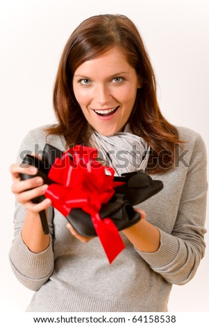 Surprised woman holding present shoes with red bow