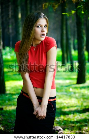 Surprised woman in a forest. Dark saturated colors. - stock photo