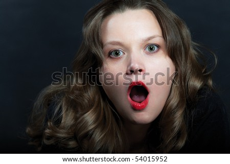Surprised woman in pearl necklace on black background - stock photo