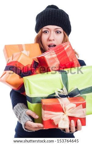 Surprised woman in winter hat holding many presents, isolated on white background. - stock photo