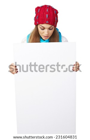 Surprised woman in winter hat peeking out of the edge of white banner and looking down at it, over white studio background - stock photo