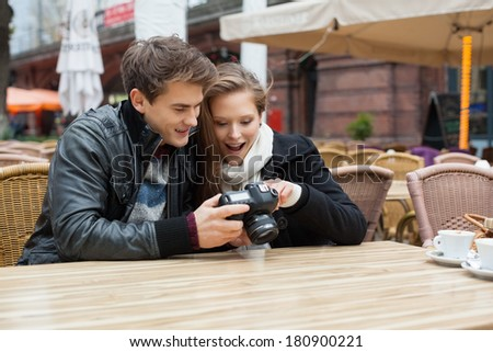 Surprised woman looking at photographs on digital camera with man at outdoor restaurant - stock photo