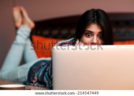 Surprised woman lying on the bed and looking at laptop