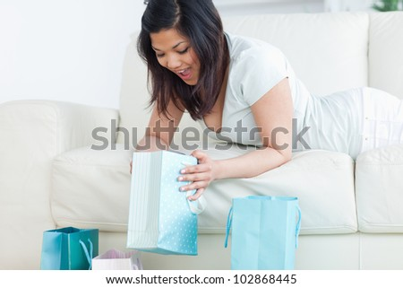 Surprised woman on a couch looking in a shopping bar in a living room - stock photo