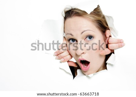surprised woman peeping through hole in paper - stock photo