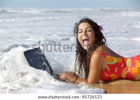 surprised woman using laptop in sea waves - stock photo