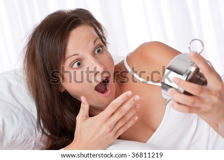 Surprised woman watching alarm clock in white bed
