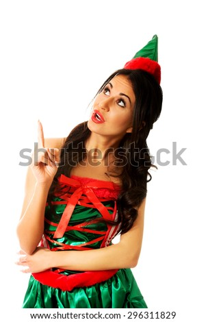 Surprised woman wearing elf clothes pointing up. - stock photo