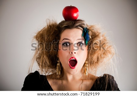 Surprised woman with a messy hairdo and an apple on top - stock photo