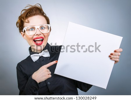 Surprised woman with blank white board on gray isolated - stock photo