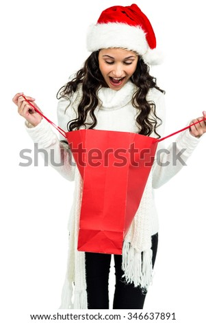 Surprised woman with christmas hat looking in red shopping bag on white screen