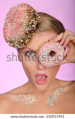 surprised woman with donut on head and in front of eye on pink background - stock photo