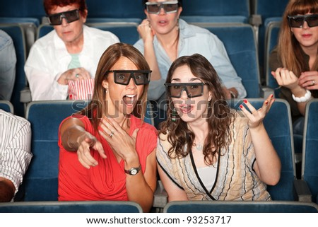 Surprised woman with friend in 3D glasses points index finger - stock photo