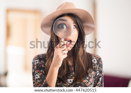 Surprised woman with magnifying glass on unfocused background - stock photo