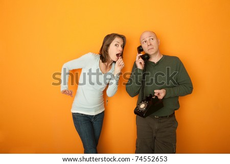 Surprised woman with man on telephone conversation - stock photo
