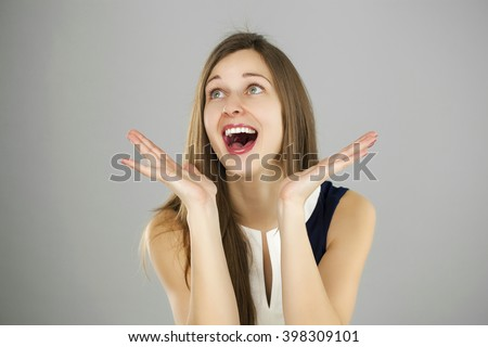 Surprised woman with opened mouth and big eyes holding hands the face and looking happy isolated on gray background  - stock photo