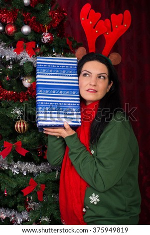 Surprised woman with reindeer ears listening to Christmas tree - stock photo