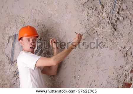 Surprised worker electric trying to fix the broken wires - stock photo