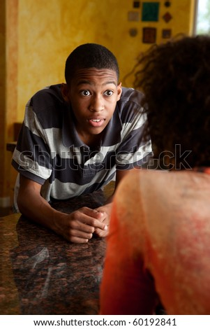 Surprised young African-American man talking to woman in kitchen