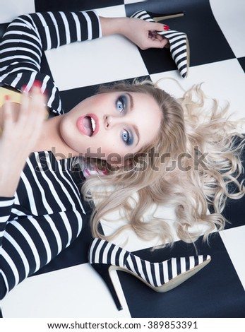 Surprised young attractive blonde woman lying down on a checkered floor with high heel stiletto shoes, fashion concept - stock photo