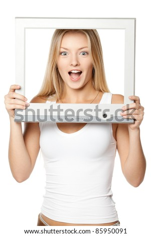 Surprised young blond female looking through the TV / computer screen frame, over white background