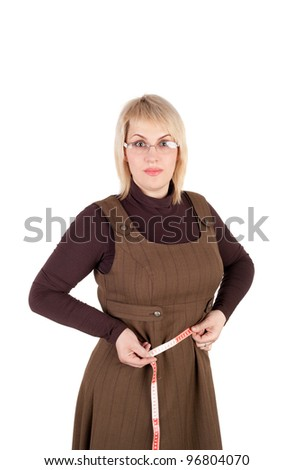 surprised young blond woman measuring her waist - stock photo