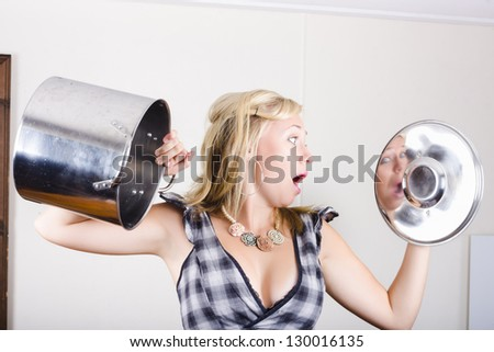 Surprised young blonde woman standing in house kitchen looking at a empty cook pot when out of ingredients in a grocery shopping concept - stock photo