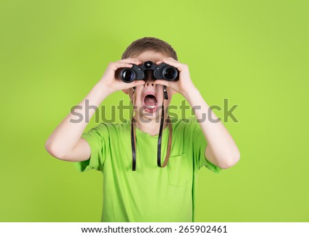 Surprised young boy with binoculars on green background. Shocked kid with open mouth looking through binoculars. - stock photo