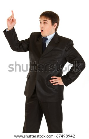 Surprised young businessman with rised finger isolated on white. Idea gesture.