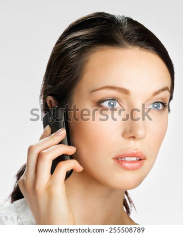Surprised young businesswoman with cell phone, on grey - stock photo