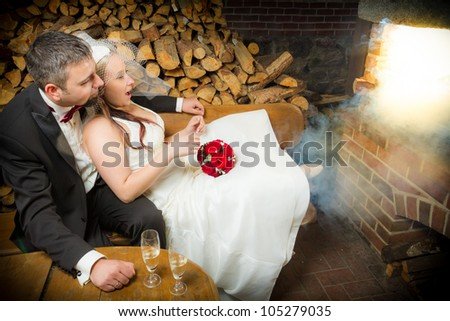 Surprised young couple sitting in front of a smoking fireplace - stock photo