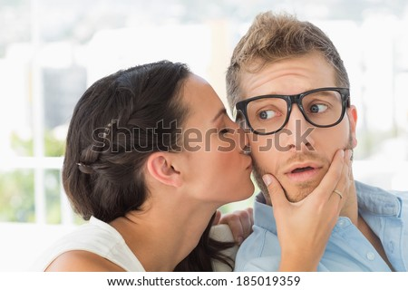 Surprised young designer getting a kiss from a co worker in creative office - stock photo