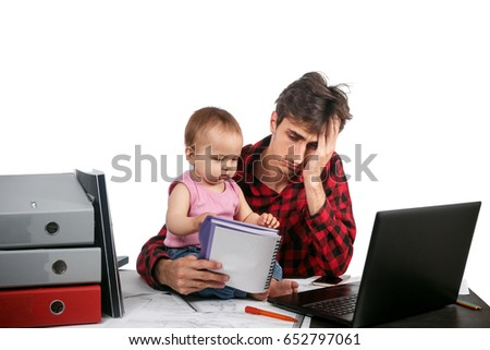 Surprised young father sits at office table with baby, documents. laptop. isolated on white