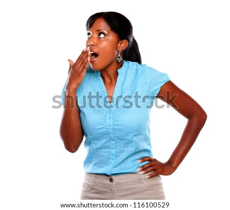 Surprised young female looking up on blue shirt against white background - copyspace - stock photo